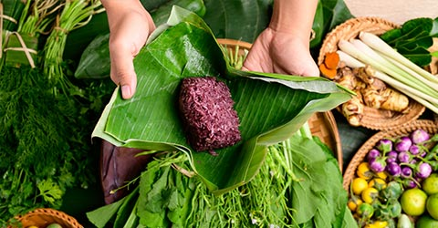 Hands wrapping purple sticky rice in banana leaves